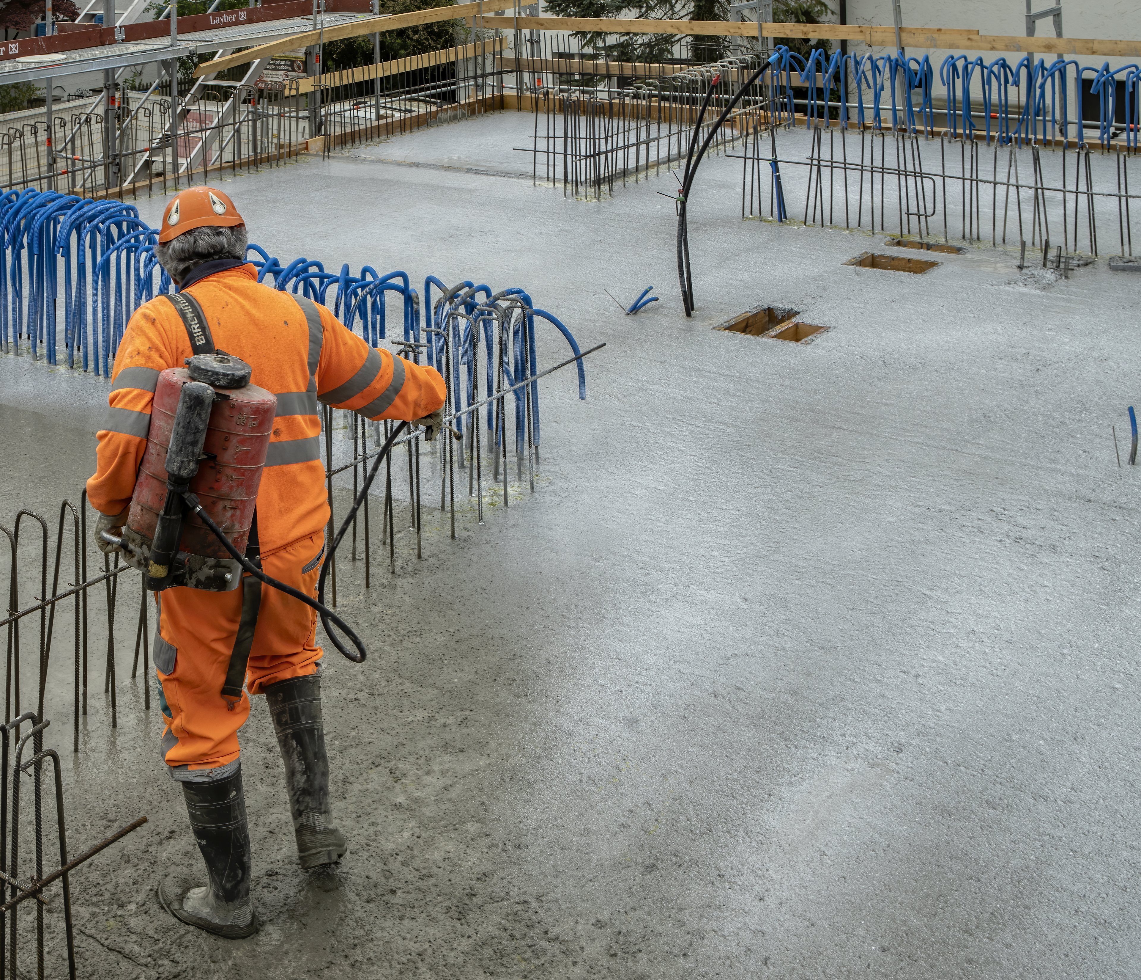 Man applying Sika® Antisol® curing compound on concrete on construction site with reinforcement