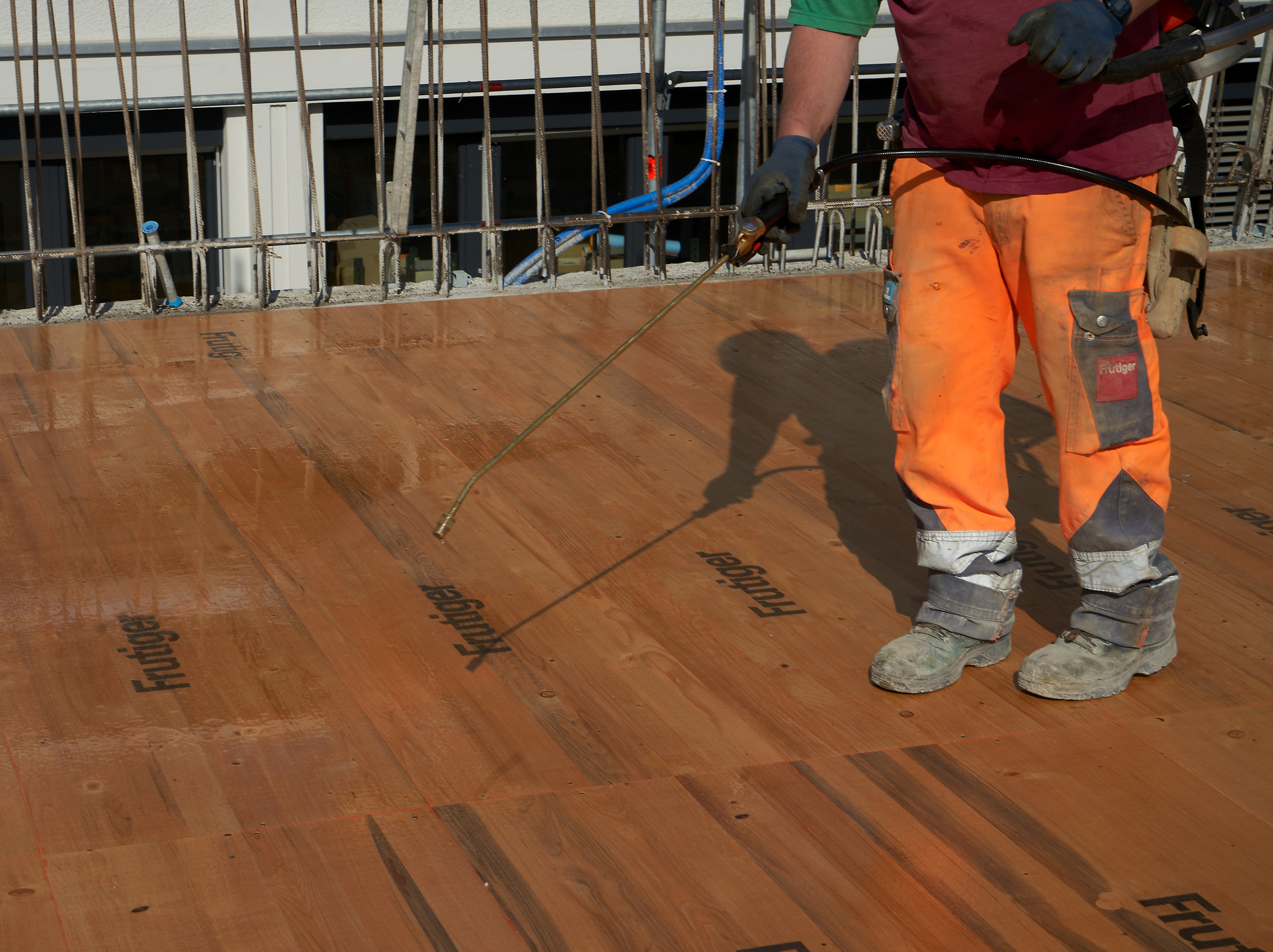 Man spraying Sika® Separol® formwork release agent on wood on construction site